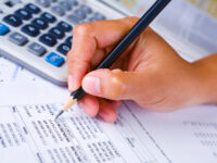 a Hand holding a pencil checking financial report, the calculator and newpaper are in the background.